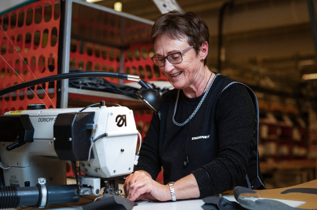 Smiling worker sewing